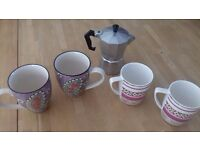 Four mugs and a coffee pot