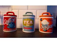Colourful, retro style tea, coffee and sugar canisters.