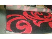 A brand new still good quality red x black patterned rug.