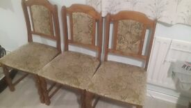 3 chairs and a wooden dining table