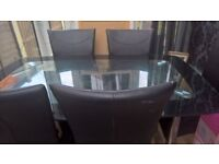 Black glass dining table with 6 black faux leather chairs