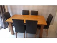 Solid oak dining table & 6 black leather chairs.