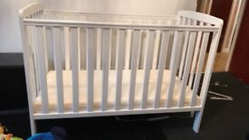 White wooden baby cot with mattress