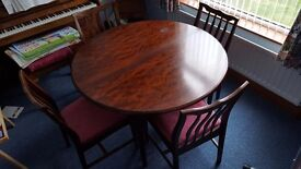 DINING TABLE: Stag Minstrel mahogany circular table with integrated extension & 4 matching chairs
