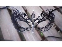 Black metal filigree face mask with diamanté accents, ideal for a masked ball or fancy dress