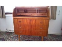 A light Oak roll top desk with 3 drawers and casters. In good condition