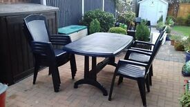 6 seater table and chairs in blue plastic, chairs have grey weave effect backs.