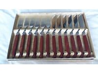Stainless steel steak knives and forks with wooden handles. Six settings, excellent condition.