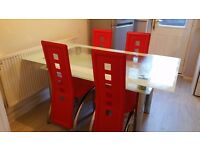 Glass table with 4 leather red chairs in good condition
