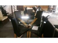 A brand new very good quality round glass topped dining table with 4 chairs.