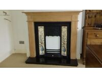 Cast iron fire with tile and pine surround, standing on a black granite hearth.