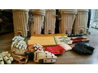 Junior cricket bats and various sized gloves and pads