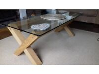 Coffee table with glass top, laminate light wood criss cross base.