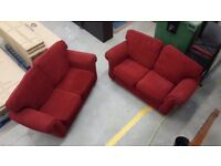 Two red fabric two seater sofas. Would fit three