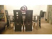 Glass dinning room table with 6 leather effect chairs.