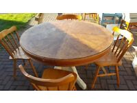 Large round wood dining table (4 chairs can be included for an additional cost)