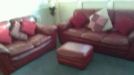 Three and two seater red real leather sofas and footstool