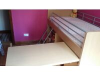 childs bunk bed with desk, storage and chair below