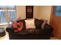 Black leather look material sofa cream & grey scatter cushions.
