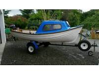 Fishing boat cuddy outboard and trailer.