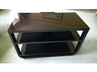 Black TV stand with three black glass shelves. Cable management at the rear. Up to 42 inch TV