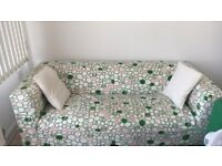 Green, pink, and white floral sofa