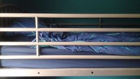Silver metal bunk beds without mattresses or bedding