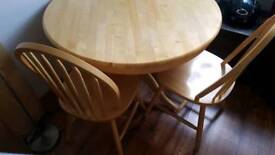 Light round dining table with 2 chairs