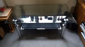 Glass coffee table very solid. 110L x 60W x 45H with fabric shelf