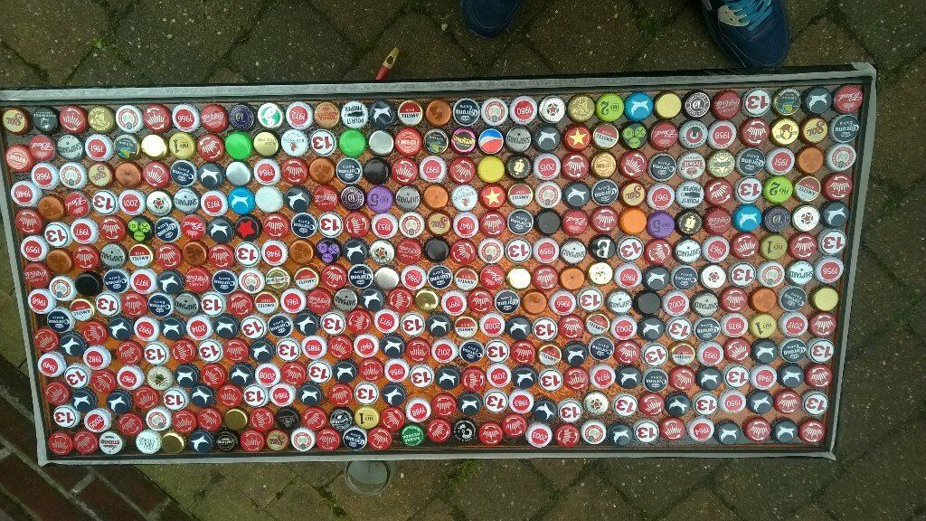 Black coffee table with beer bottle tops set in a clear reasin / varnish.