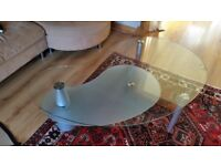 Stylish modern kidney shaped glass coffee table with rotating lower shelf excellent condition.