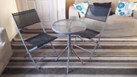 Glass table and 2 folding chairs. Less of one year in used.