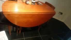A vintage teak dining table with fold down leaves