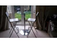 Tall, glass topped kitchen/breakfast table and two folding chairs.