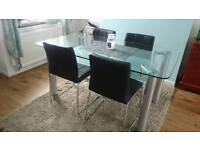 Glass table and black leather chairs