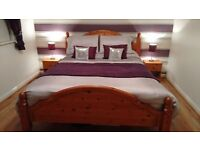 SOLID PINE KINGSIZE BED FRAME (MATTRESS NOT INCLUDED) WITH MATCHING BEDSIDE CABINETS.