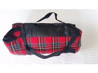 Fold up red tartan waterproof picnic rug with carrying handle and strap