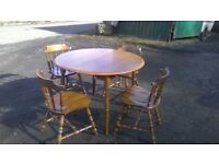 Beautiful stained pine extending dining table and four matching chairs