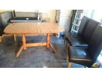 Solid pine dining room table and four brown faux leather chairs