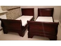 Two solid dark wood single sleigh bed frames and mattresses