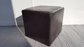 Cube seating/stool in chocolate brown faux leather finish.