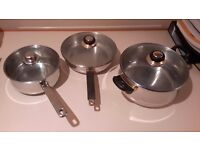 3 Stainless Steel Saucepans with glass lids.