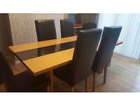 For sale and ready to go now. Large oak table with centre peice of granit with 6 black chairs
