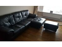 Black leather corner sofa, arm chair and foot rest. Suite in great condion