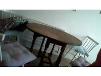 Brown wooden table with spindle legs and four chairs.