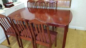 Wooden dining table with 8 chairs. Used in good condition.