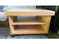 Pine effect coffee table, two lower shelves and on wheels