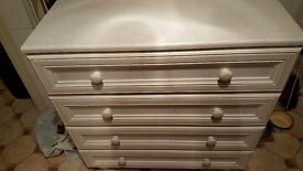 A white four drawer chest of drawers in excellent condition
