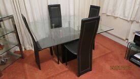 Dining room table ,Glass by Furniture Village with four chairs
