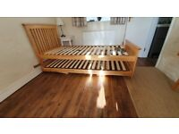 Single to super king wooden bed frame using single pull out bed underneath.
